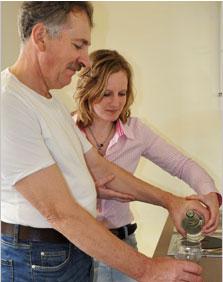 Ergotherapie Neurologie, Bereich Selbstversorgung, Herr S. schüttet sich Wasser ein