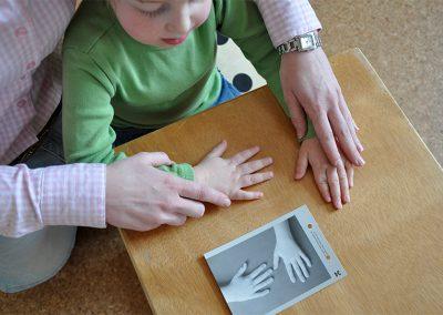Moritz positioniert seine Hände, wie er es auf dem Bild sieht